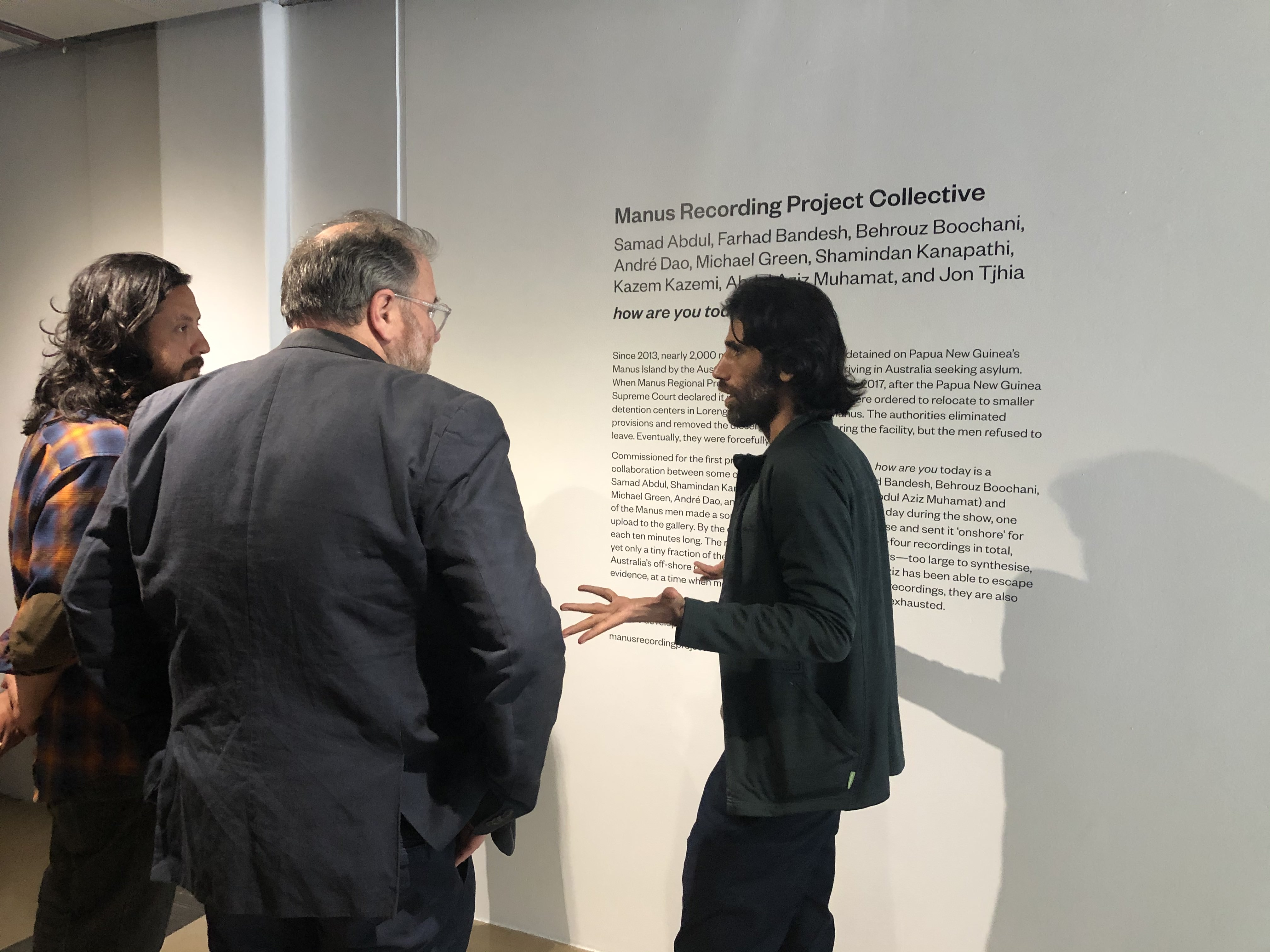 <p>Behrouz Boochani (right) with artist Bryan Philips and curator Robert  Leonard, next to the work <em>how are you today</em> by Manus Recording Project Collective, City Gallery Wellington, November 17, 2019.</p>