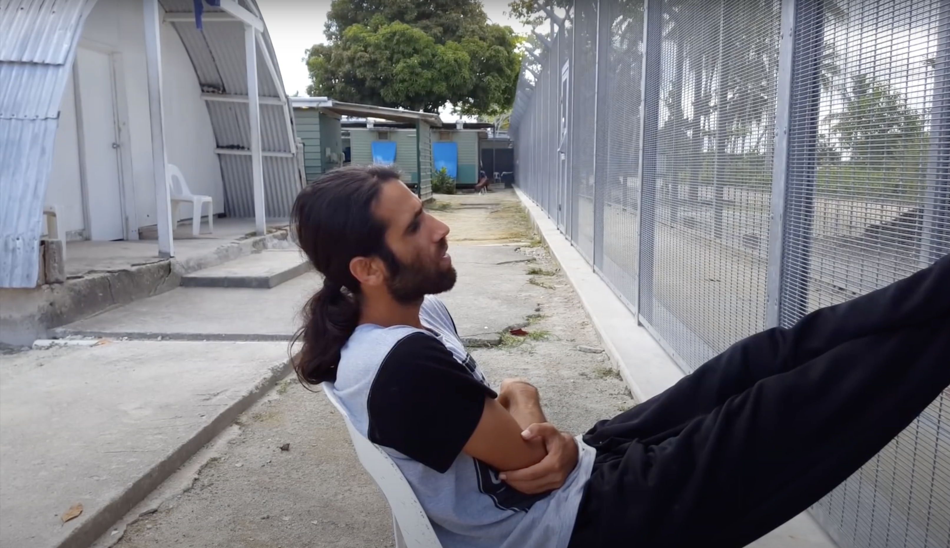 <p>Arash Kamali Sarvestani and Behrouz Boochani, <em>Chauka, Please Tell Us The Time</em> (2017), video still, depicting Behrouz Boochani by the fence at Manus Regional Processing Centre, before its closure and detainees were moved to other facilities on the island.</p>